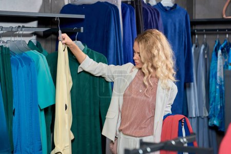attractive young woman choosing clothes in boutique