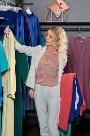 attractive young woman choosing clothes in fashion store