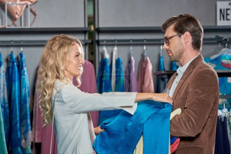 side view of couple choosing fashionable clothes in showroom