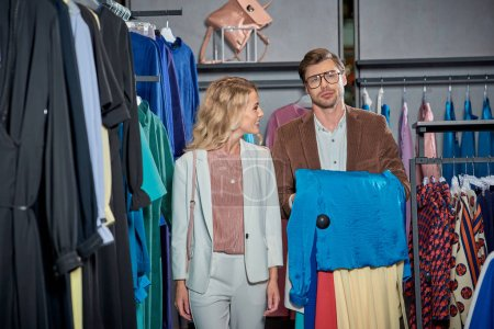 Photo for Young couple choosing stylish clothes in showroom - Royalty Free Image