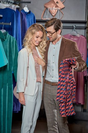 smiling young couple shopping together in boutique