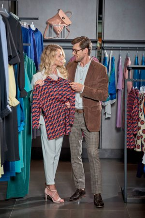 Photo for Young couple smiling each other while shopping together in boutique - Royalty Free Image
