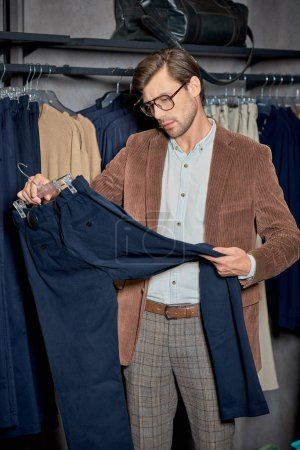 Photo for Handsome man in eyeglasses holding hanger with stylish pants in boutique - Royalty Free Image