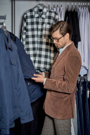 handsome man in eyeglasses looking at jacket while shopping in boutique