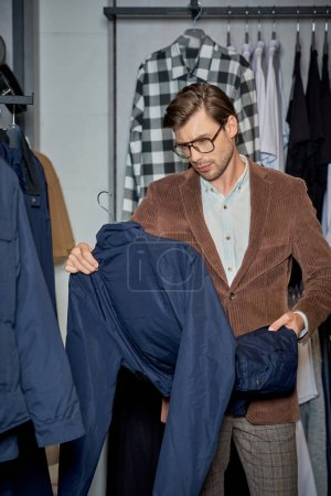 handsome man in eyeglasses holding jacket while shopping in boutique