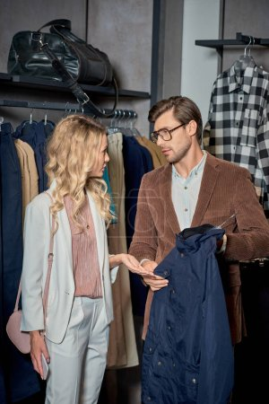 Photo for Young couple talking and looking at each other while shopping together - Royalty Free Image
