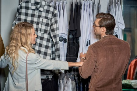 back view of young couple choosing stylish clothes together in boutique