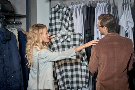 young couple choosing stylish clothes together in boutique