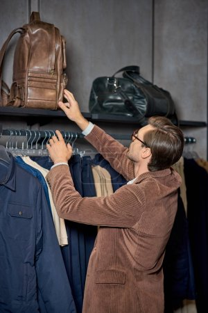 Photo for Young man in eyeglasses holding backpack while shopping in boutique - Royalty Free Image