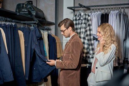 Foto de Sonriente mujer joven mirando a hombre guapo eligiendo ropa en tienda - Imagen libre de derechos