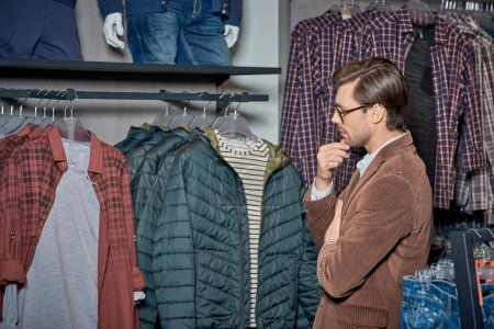 Photo for Handsome young man with hand on chin looking at stylish clothes in boutique - Royalty Free Image