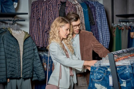 Photo for Smiling young couple choosing stylish clothes in boutique - Royalty Free Image