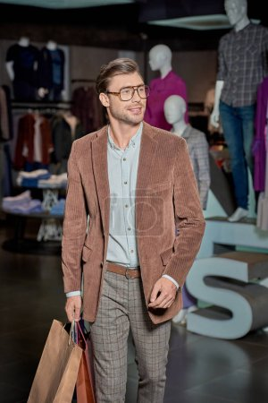 handsome smiling man in eyeglasses holding shopping bags and looking away in fashion store