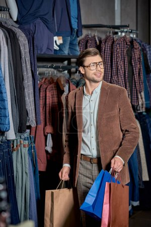 Photo for Handsome smiling man holding paper bags and looking away in store - Royalty Free Image
