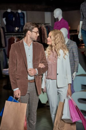 Photo for Happy young couple with shopping bags smiling each other in boutique - Royalty Free Image