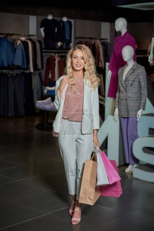 Photo for Beautiful young woman holding shopping bags and smiling at camera in fashion store - Royalty Free Image