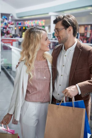happy young couple with shopping bags smiling each other in mall