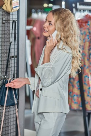 smiling young woman talking by smartphone and shopping in fashion store