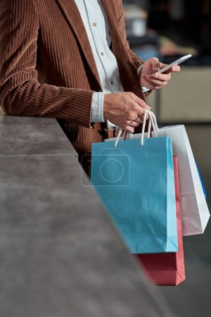 cropped shot of man holding shopping bags and using smartphone in store