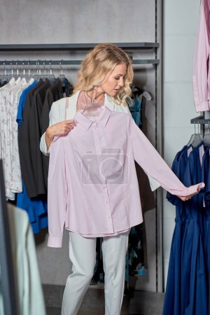 beautiful young woman holding hanger with stylish shirt in boutique