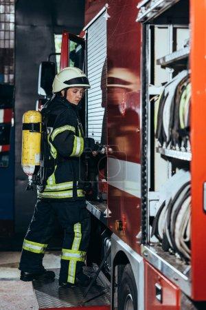 Foto de Vista lateral del bombero femenino con extintor de incendios en el camión de cierre trasero en la estación de bomberos - Imagen libre de derechos