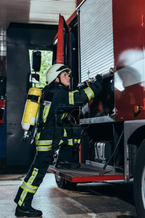 side view of female firefighter with fire extinguisher on back closing truck at fire department