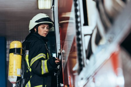 side view of female firefighter with fire extinguisher on back closing truck at fire station