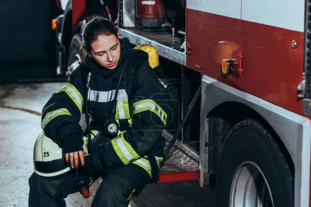 Photo for Tired female firefighter in uniform with helmet sitting on truck at fire station - Royalty Free Image