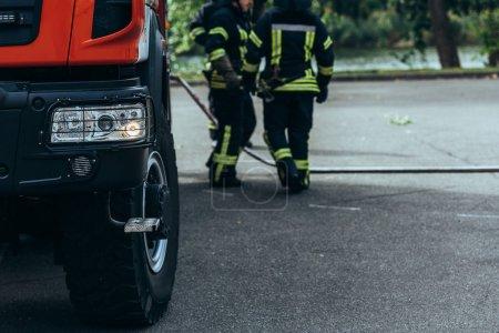Photo pour Vue partielle de la brigade de pompiers et de tuyau d'arrosage sur le terrain sur la rue - image libre de droit