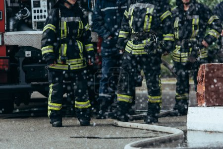 partial view of brigade of firefighters and water hose on ground on street