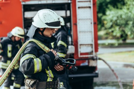 selective focus of male firefighter in helmet with water hose on street
