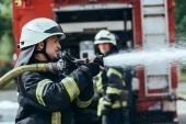 """Постер, картина, фотообои """"выборочный фокус пожарный с водой шланг тушения пожара на улице"""""""