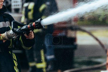 Foto de Vista parcial del bombero con la manguera de agua, extinción de fuego en la calle - Imagen libre de derechos