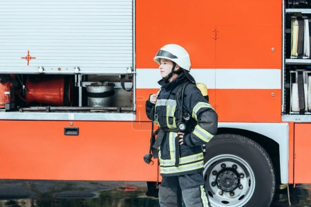 Photo for Female firefighter in protective uniform standing on street with red fire truck behind - Royalty Free Image
