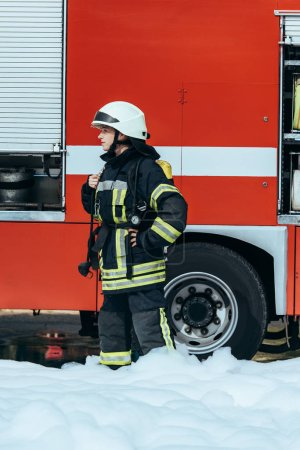 female firefighter in protective uniform standing in foam on street with red fire truck behind