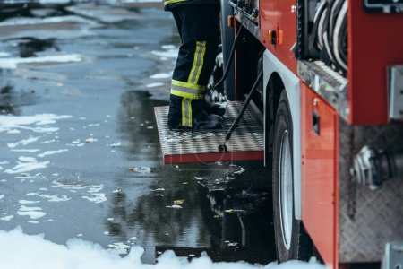 cropped shot of firefighter in fireproof uniform standing on fire truck on street