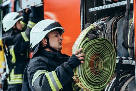 male firefighter in helmet putting water hose into truck on street