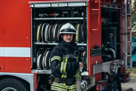 portrait of fireman in protective uniform and helmet standing at truck with water hoses inside on street