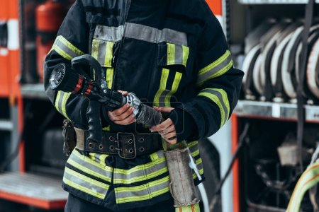 cropped shot of firefighter in protective uniform holding water hose in hands