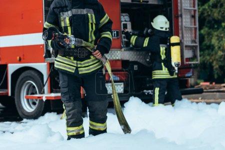 Foto de Tiro recortado de bombero en manguera de agua en las manos de pie en espuma en la calle - Imagen libre de derechos