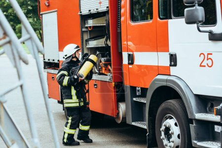 female firefighter in protective uniform putting fire extinguisher into truck on street