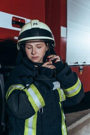 Foto de Retrato de mujer bombero en uniforme control de casco en el Departamento de bomberos - Imagen libre de derechos