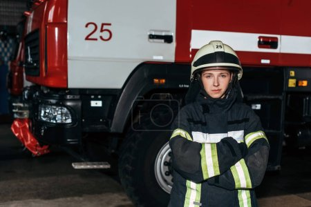 Photo for Portrait of female firefighter in helmet with arms crossed standing at fire station with truck behind - Royalty Free Image