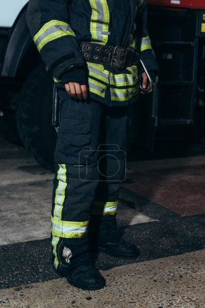 partial view of firefighter in protective fireproof uniform standing at fire department