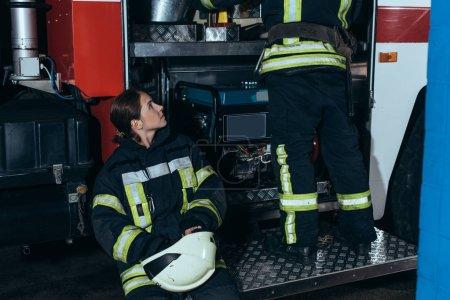 Foto de Vista parcial de mujer bombero en casco viendo colega revisar equipo en estación de bomberos - Imagen libre de derechos