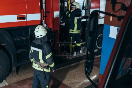 partial view of firefighters in fireproof uniform and helmets at fire station