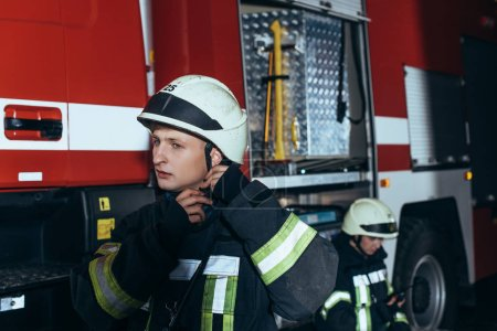 firefighter checking helmet with colleague behind at fire department