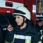 Female firefighter talking on portable radio set w...