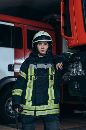 portrait of female firefighter in protective uniform with portable radio set at fire department