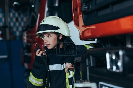 portrait of female firefighter in protective uniform talking into  portable radio set at fire station